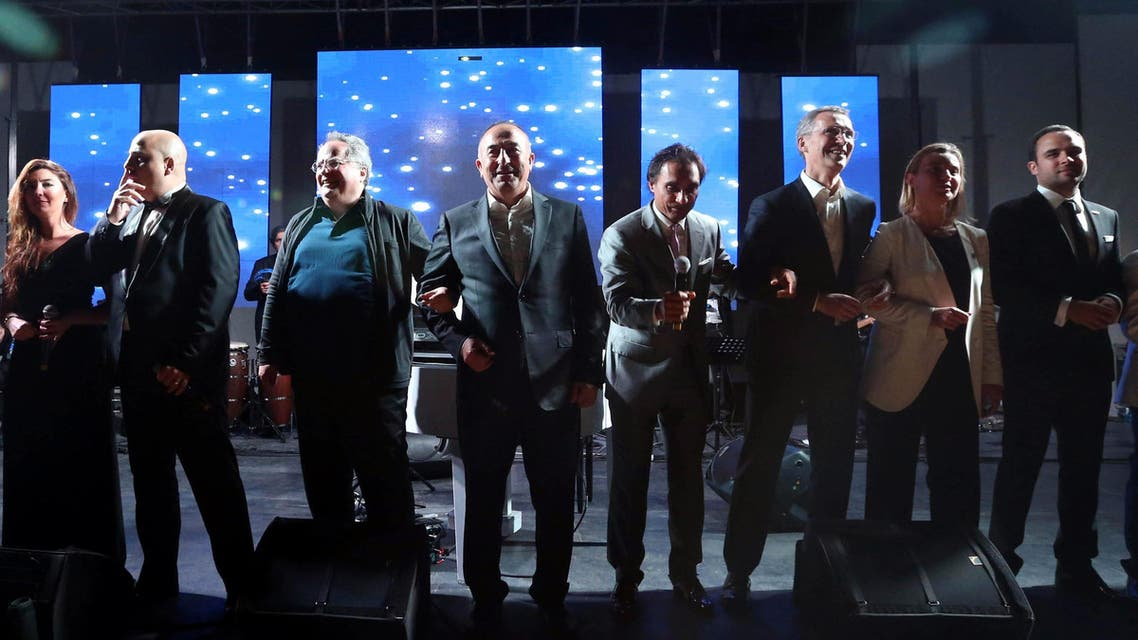 """Secretary General of NATO, Jens Stoltenberg, third right, Turkish Foreign Minister Mevlut Cavusoglu, center, Greek Foreign Minister Nikos Kotzias, third left, EU High representative for foreign policy Federica Mogherini, second right, and other NATO officials dance to """"We are the world """" after a dinner during the NATO Foreign Ministers' conference in Antalya, Turkey, Wednesday, May 13, 2015."""
