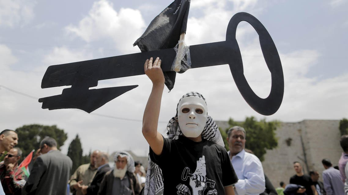 A Palestinian wearing a mask holds a cut-out of a key during a rally ahead of the Nakba day in the West Bank city of Bethlehem May 14, 2015. (File: Reuters)