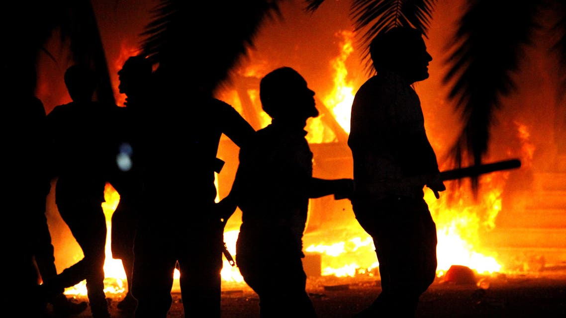 In this Friday, Sept. 21, 2012 file photo, Libyan civilians watch fires at an Ansar al-Shariah Brigades compound, after hundreds of Libyans, Libyan Military, and Police raided the Brigades base, in Benghazi, Libya.  (AP)