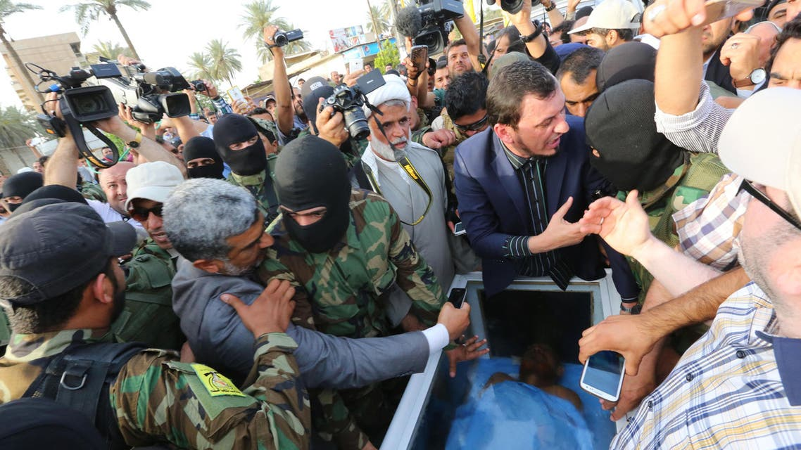 Civilians and members of the Iraqi Hezbollah Brigades gather around a glass-topped coffin as they prepare to deliver what they claim is the body of former Saddam Hussein deputy Izzat Ibrahim al-Douri in Baghdad, April 20, 2015 (AP)