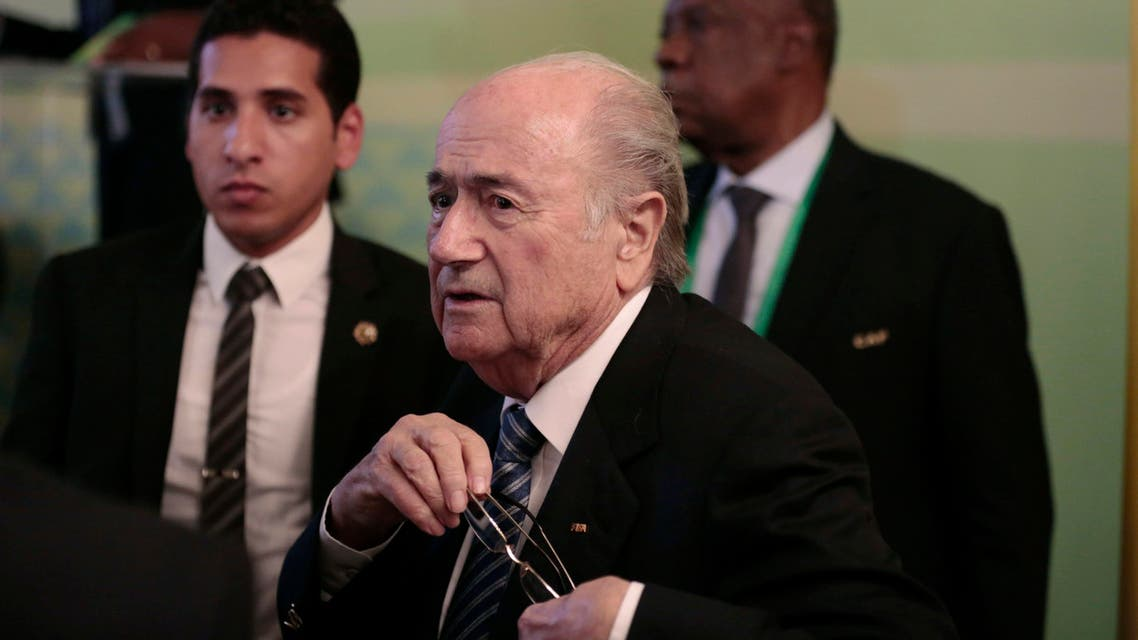 FIFA President Sepp Blatter, center, and Confederation of African Football President Issa Hayatou, back right, leave a press conference in Cairo, Egypt, Tuesday, April 7, 2015. (AP)