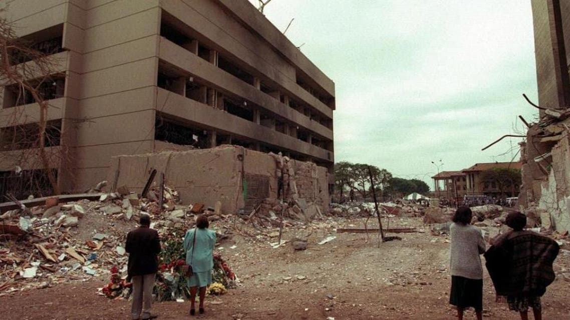 This August 7, 1998, file image shows Kenyan residents looking at the US embassy (L) days after the bomb blast that killed 224 people in the East African nation (AFP)