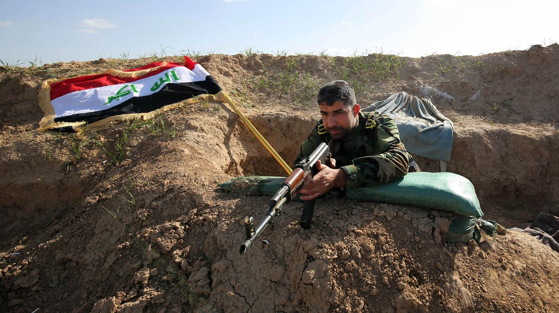In this Sunday, Feb. 15, 2015 photo, a Shiite militia fighter aims his weapon with the Iraqi flag in the background. (AP)