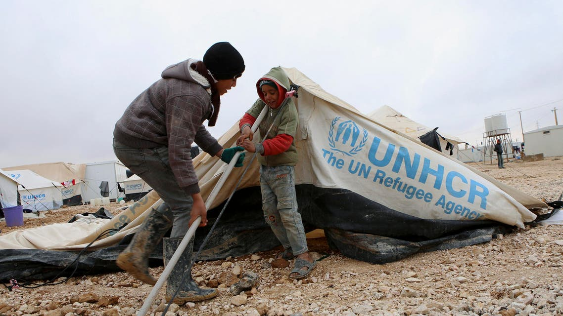 Syrian refugee children try to put up their tent that has fallen over the recent stormy days at Zaatari Syrian refugee camp in Mafraq, Jordan, Sunday, Jan. 11, 2015. (AP Photo/Raad Adayleh)