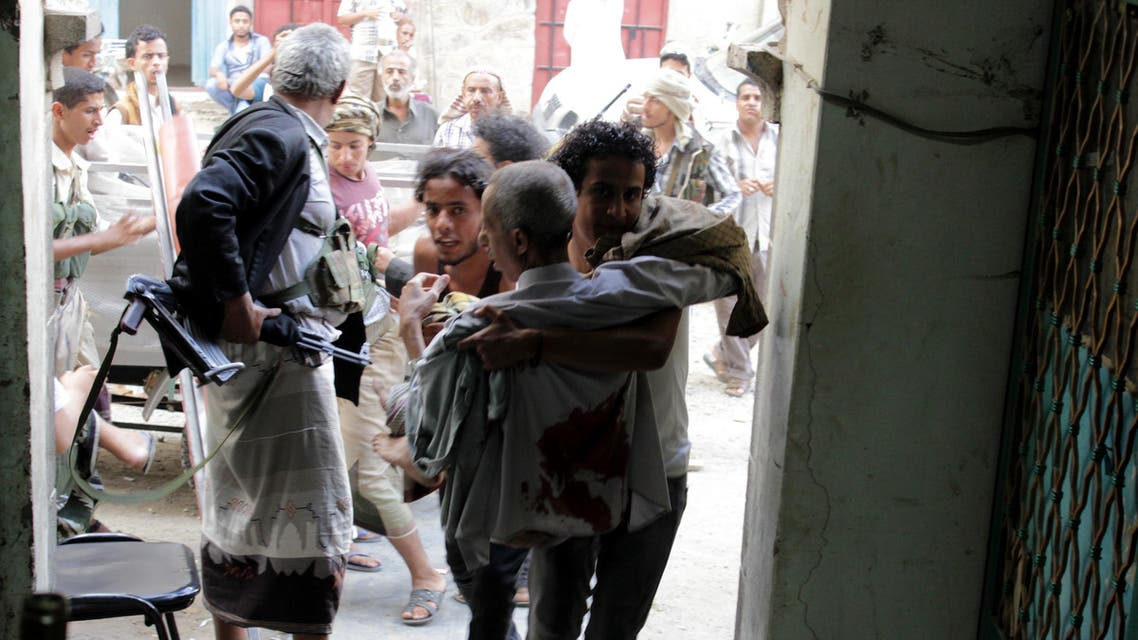 People carry a man, who was injured during a clashes between tribal fighters and Shiite militia known as Houthis, in the western city of Taiz, Yemen, Friday, May 15, 2015. Fighting was underway across Yemen on Friday, the third day of a humanitarian truce between a Saudi-led coalition and Shiite rebels, as the U.N. envoy pushed for holding peace talks in Geneva. (AP Photo/Abdulrahman Hawis)