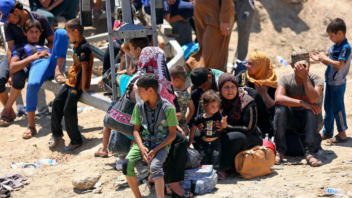 Displaced Iraqis from Ramadi rest before crossing the Bzebiz bridge after spending the night walking towards Baghdad, as they flee their hometown, 65 km west of Baghdad, Iraq, Saturday, May 16, 2015.  AP