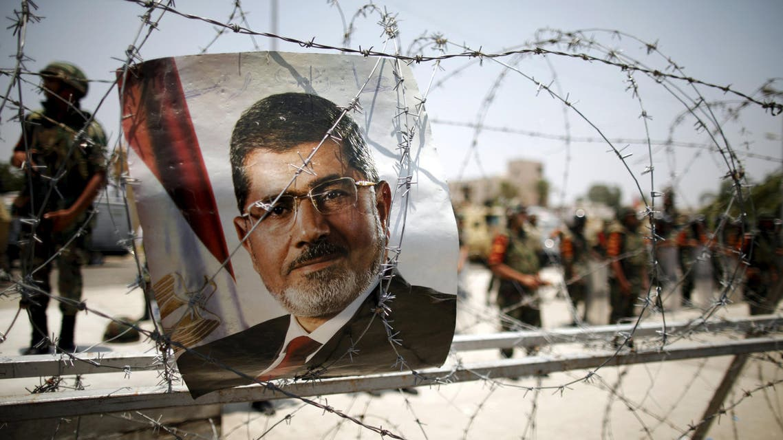 File picture shows a portrait of deposed Egyptian President Mohamed Mursi on barbed wire outside the Republican Guard headquarters in Cairo. (Reuters)