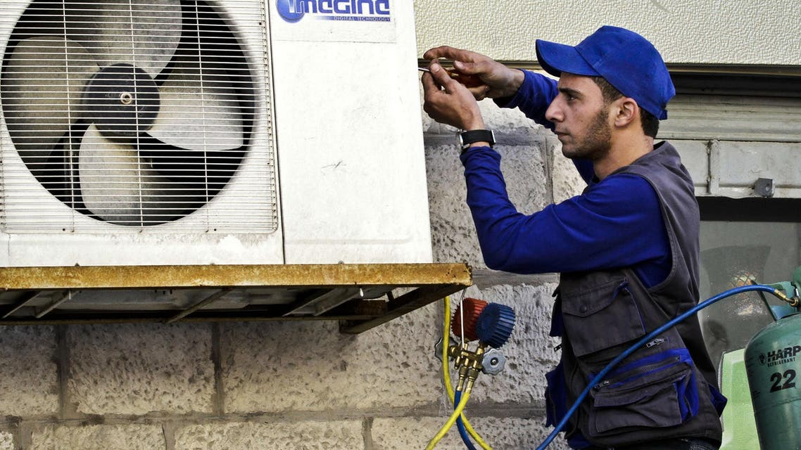 Mohammed Nabouti, a 21-year-old technician, fixes the air conditioner of a shop in Amman, Jordan AP
