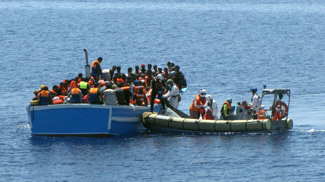 This photo provided by the Italian Navy's Press Office Monday, May 4, 2015 shows members of an an Italian Navy unit, on the dinghy at right, as they rescue migrants in the Mediterranean Sea. (AP)