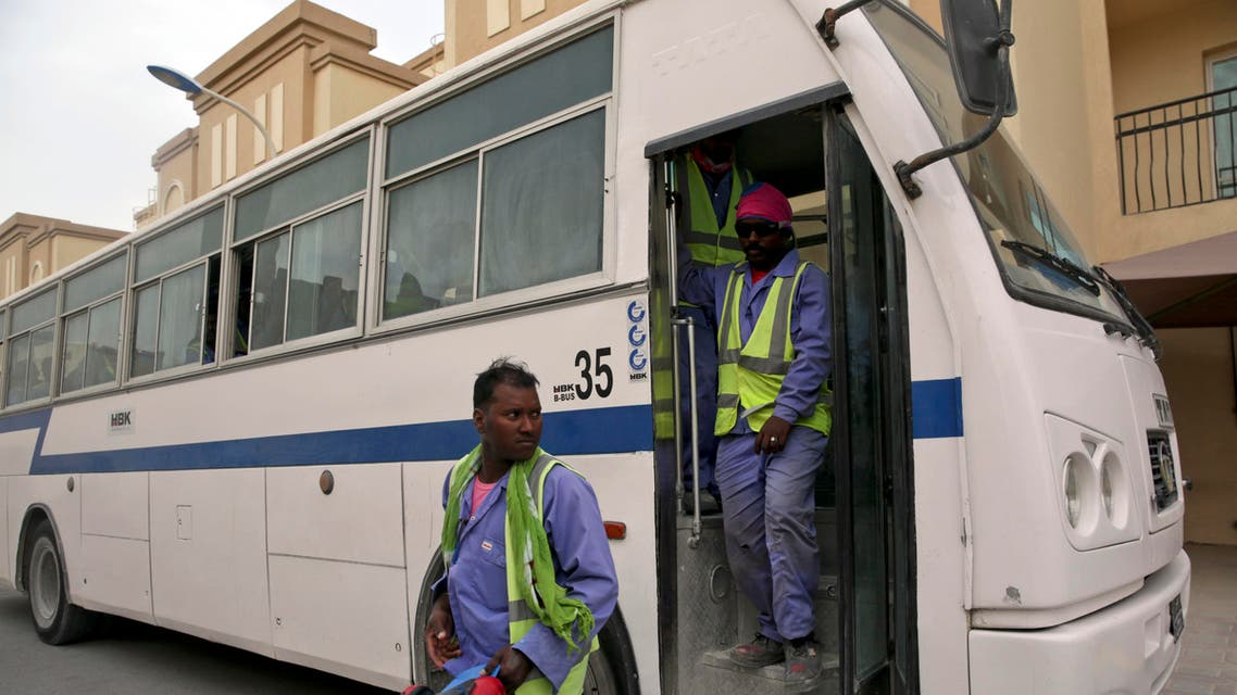 In this photo taken during a government organized media tour, foreign workers arrive at their housing facility after their shift building the Al-Wakra Stadium for World Cup in Doha, Qatar, Monday, May 4, 2015.