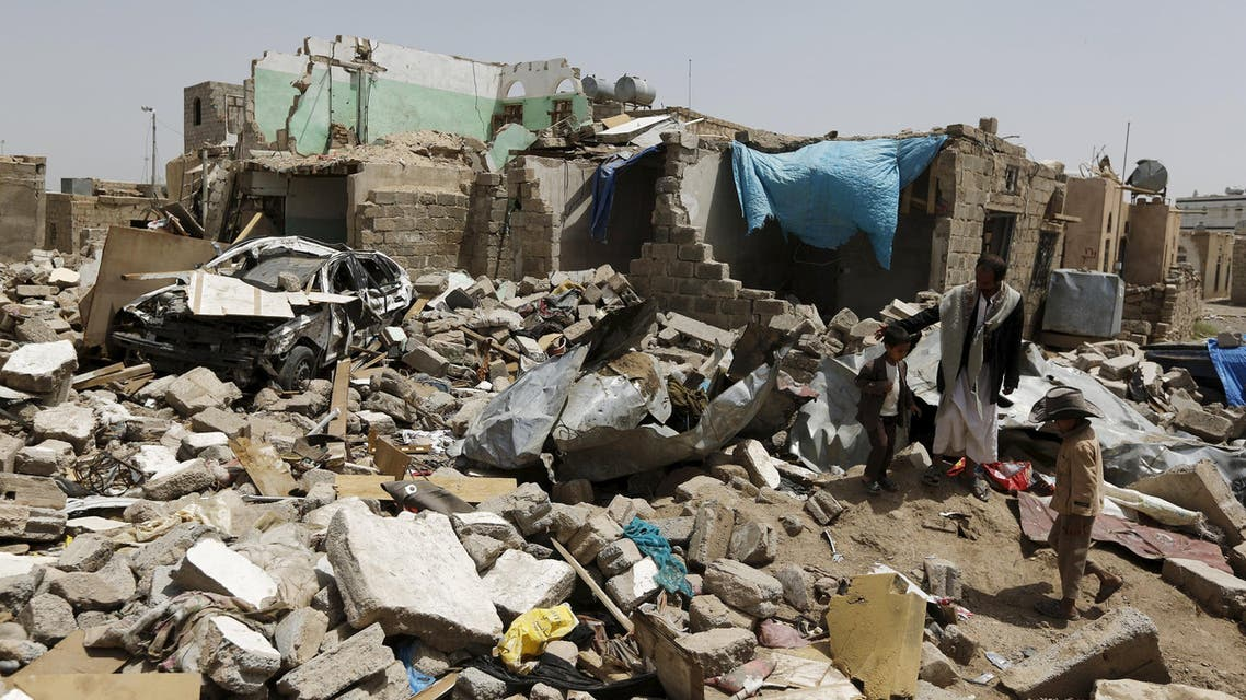 People stand at the site of a Saudi-led air strike that hit a residential area last month near Sanaa airport, May 18, 2015. Reuters