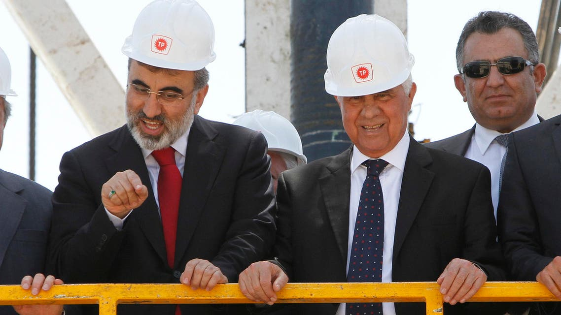 Turkish Energy Minister Taner Yildiz, left, talks to journalists with Turkish Cypriot leader Dervis Eroglu, second right, from the drilling platform during a ceremony marking the start of exploratory oil and gas drilling by Turkey in breakaway Turkish Cypriot northern half of ethnically split Cyprus, near Sinirustul/Syngkrasi, village, on Thursday, April 26, 2012. The move counters an offshore gas search by rival Greek Cypriots in the island's internationally recognized southern half that has touched off vociferous protests from Ankara and Turkish Cypriots. (AP Photo/Petros Karadjias)