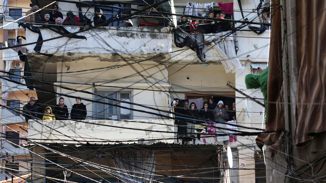 Alawite mourners seen through electricity wires stand on their balconies watching the funeral procession of those who were killed at a coffee shop where a suicide bombing struck it Saturday night, in a predominantly Alawite neighborhood of the northern port city of Tripoli, Lebanon, Sunday, Jan. 11, 2015. Syria's al-Qaida-linked Nusra Front claimed responsibility on Twitter for the blast that killed several people and wounded more than 30 in Tripoli's neighborhood of Jabal Mohsen, saying it was a twin suicide attack. (AP Photo/Hussein Malla)