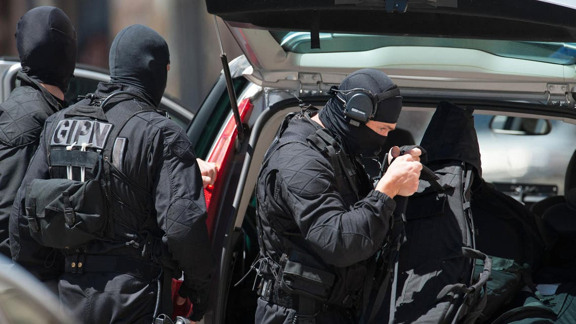 Elite police officers from the GIPN brigade arrive at a bank after a gunman took four people hostage in a bank in the southern French city of Toulouse and fired a shot, police said, Wednesday, June 20, 2012.AP