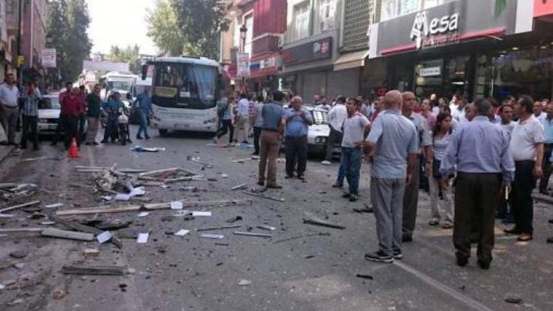 People stand at the site of an explosion at the office of pro-Kurdish People's Democratic Party (HDP) in Mersin on May 18, 2015