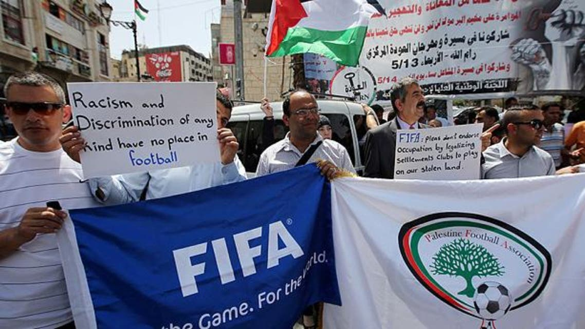 Palestinians hold banners as they demonstrate in Ramallah demanding the expulsion of Israel from FIFA AFP