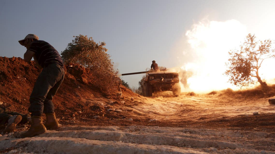Rebel fighter fires a vehicle's weapon during what the rebels said is an offensive to take control of the al-Mastouma army base near Idlib city