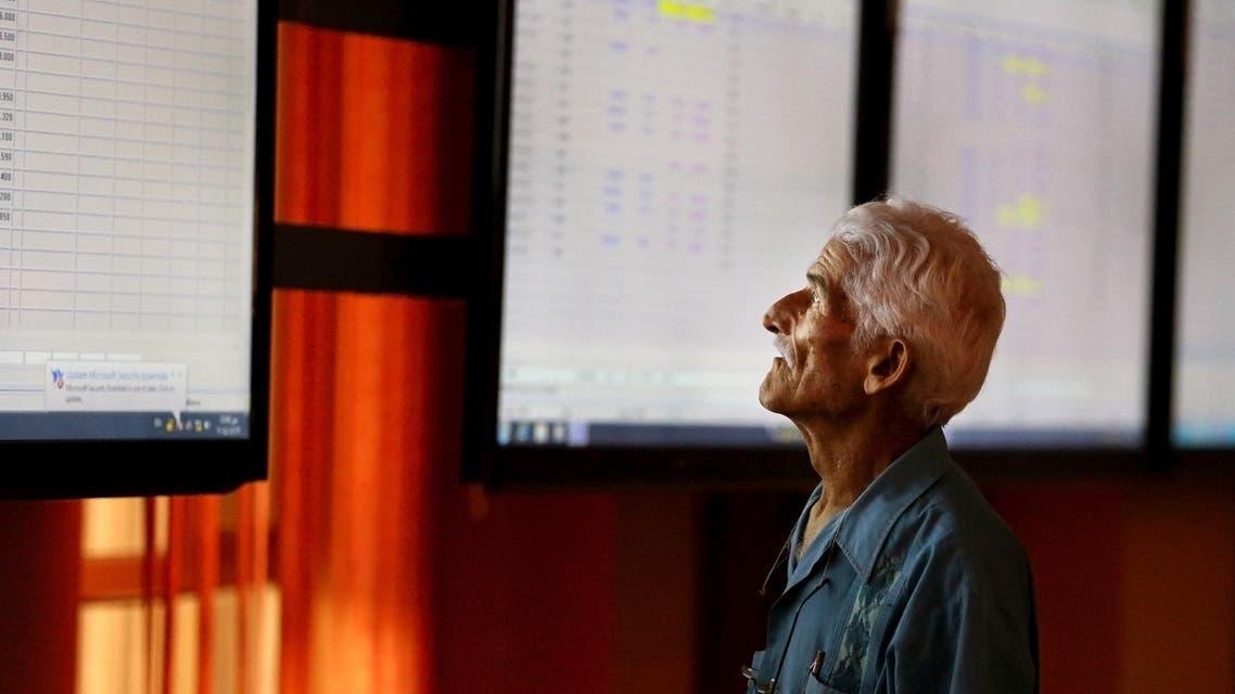 An Iraqi man checks shares prices at the Iraq Stock Exchange market in Baghdad, Tuesday, Aug. 19, 2014. (AP Photo/Hadi Mizban)