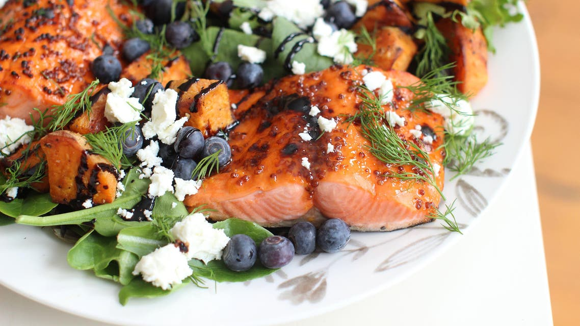 This March 16 2015 photo shows broiled sockeye salmon with blueberries and sweet potatoes in Concord, NH. (AP Photo/Matthew Mead