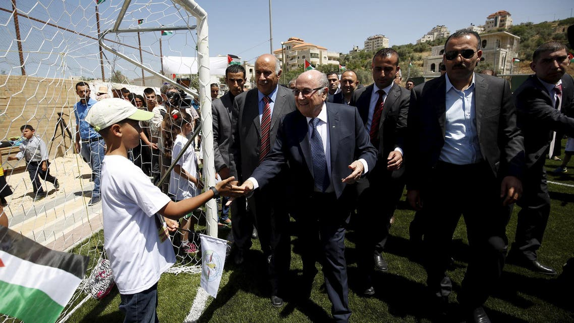 FIFA chief Sepp Blatter shakes hands with a Palestinian boy during his visit to Dura al-Qar' village in the West Bank city of Ramallah. Reuters