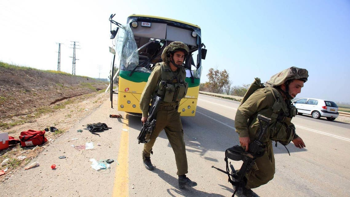 Israeli soldiers check a bus that was damaged by an anti-tank missile fired from the Gaza Strip into southern Israel on the road between kibbutz Nahal Oz and kibbutz Sa'ad April 7, 2011. (BAZ RATNER/REUTERS)