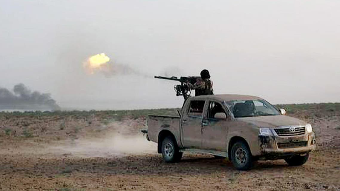 In this picture released on Wednesday, May 20, 2015 by the website of Islamic State militants, an Islamic State fighter fires his weapon during a battle against Syrian government forces on a road between Homs and Palmyra, Syria.  (AP)