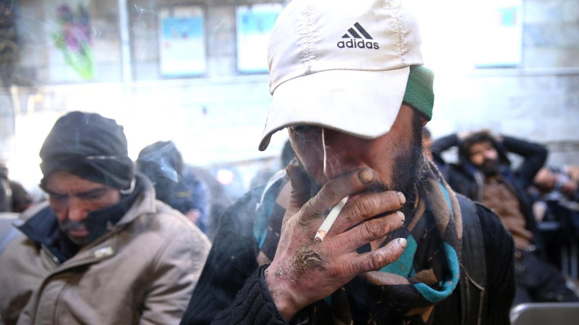 A drug addict smokes cigarette at drop-in center and shelter south of Tehran, Iran. (File: AP)