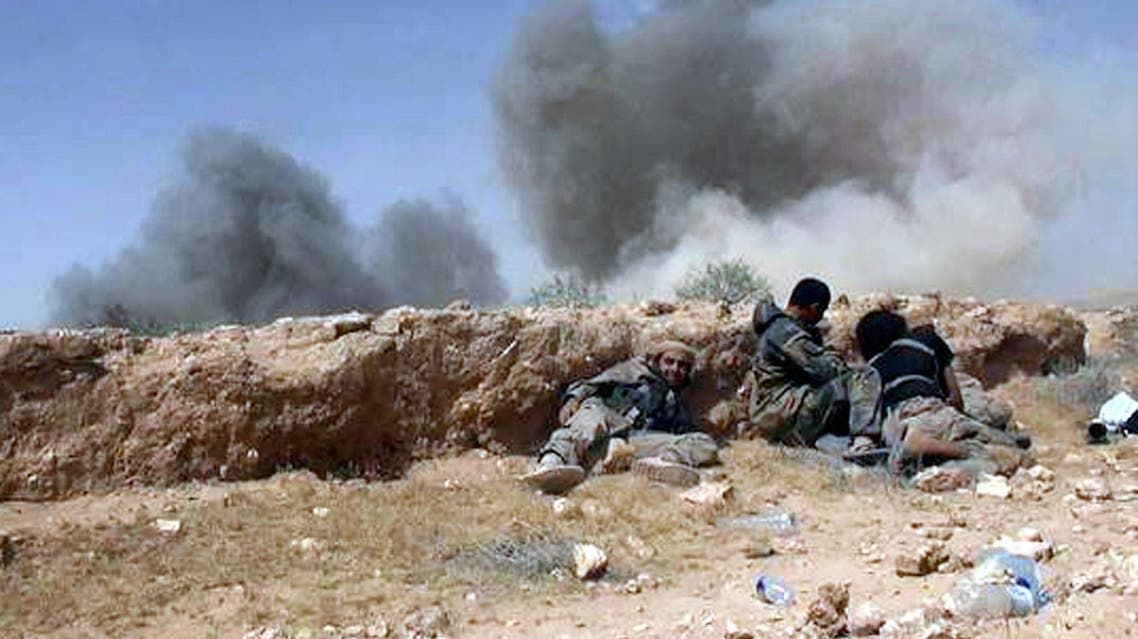 ISIS fighters take cover during a battle against Syrian government forces on a road between Homs and Palmyra, Syria. (File: AP)