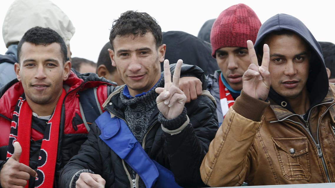Moroccan citizen Touil Abdelmajid (R) makes a victory sign as he arrives with migrants on the Italian navy ship Orione at Porto Empedocle harbour in Sicily February 17, 2015. (Reuters)