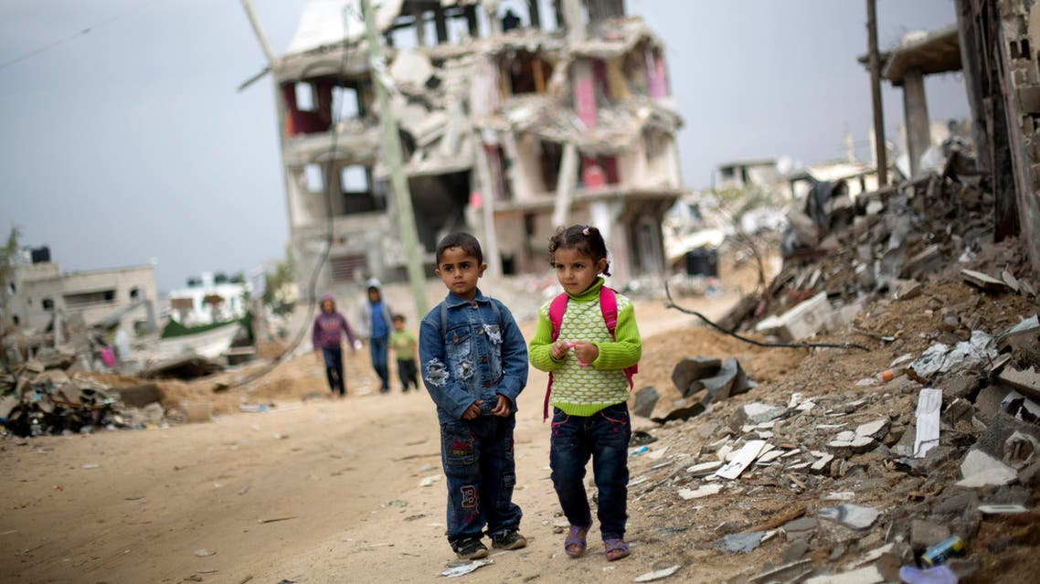 Palestinian school children walk through destroyed houses in Gaza City's Shijaiyah neighborhood, Sunday, Oct. 19, 2014. (AP)