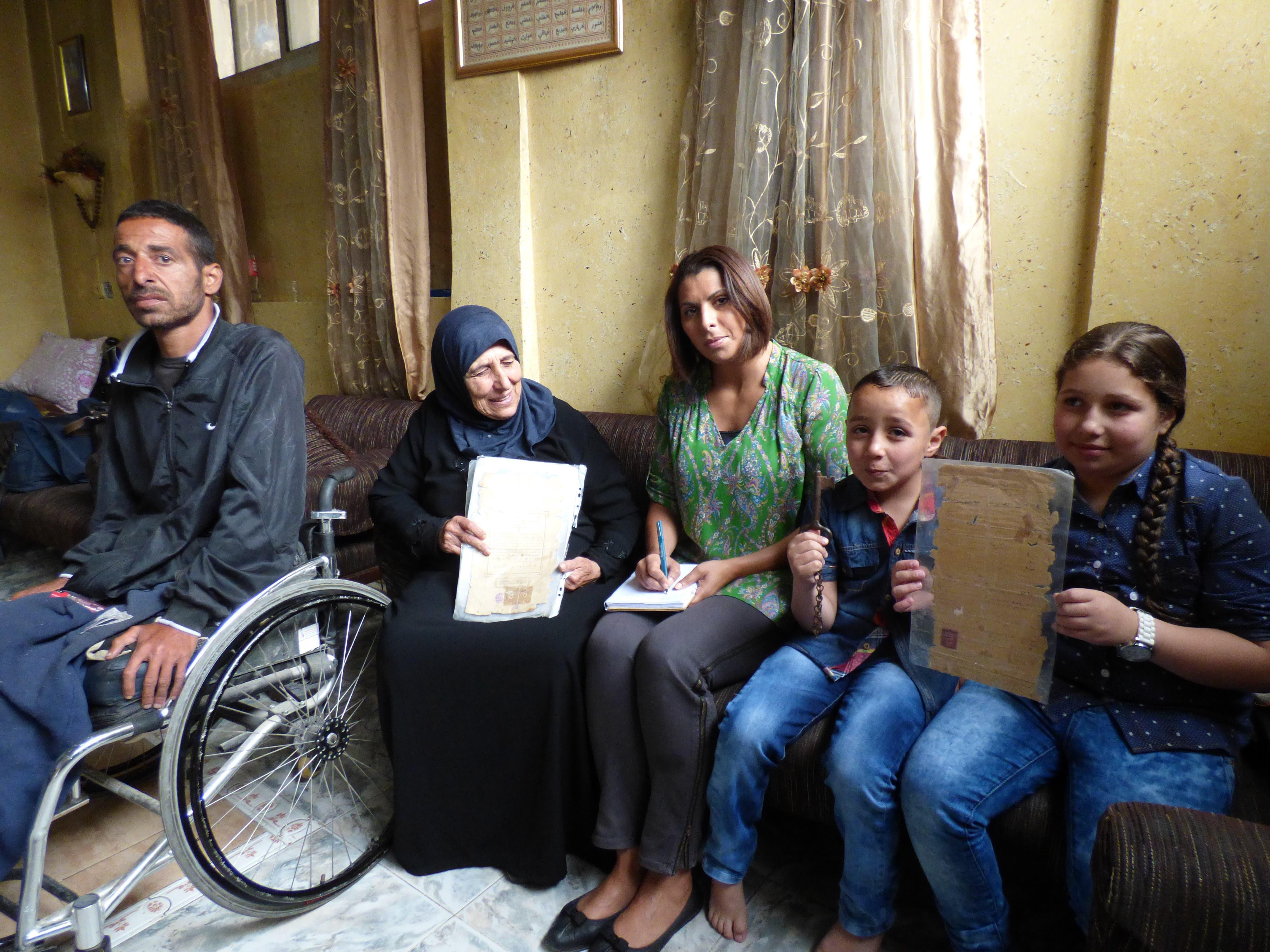 Journalist Nabila Ramdani with Fatma Hussein Omar, 67, with her son Ahmed, 37, paralysed by the Israeli army and her grandchildren Ali, 7 and Angham, 9 - holding the key and legal documents of the family home confiscated by Israel's Zionist paramilitaries in 1948. (Al Arabiya/ Nabila Ramdani)