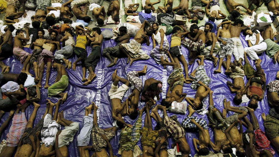 Migrants believed to be Rohingya rest inside a shelter after being rescued from boats at Lhoksukon in Indonesia's Aceh Province May 11, 2015. Nearly 600 migrants thought to be Rohingya refugees from Myanmar were rescued from two wooden boats stranded off the coast of Indonesia's northern Aceh province, authorities said on Sunday. The overcrowded boats, which were carrying nearly 100 women and dozens of children among the refugees, were towed to shore by fishermen after running out of fuel. REUTERS/Roni Bintang TPX IMAGES OF THE DAY