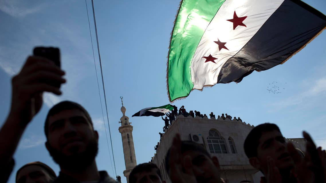 Men hold revolutionary Syrian flags during an anti-government protest in a town in northern Syria. (File: AP)