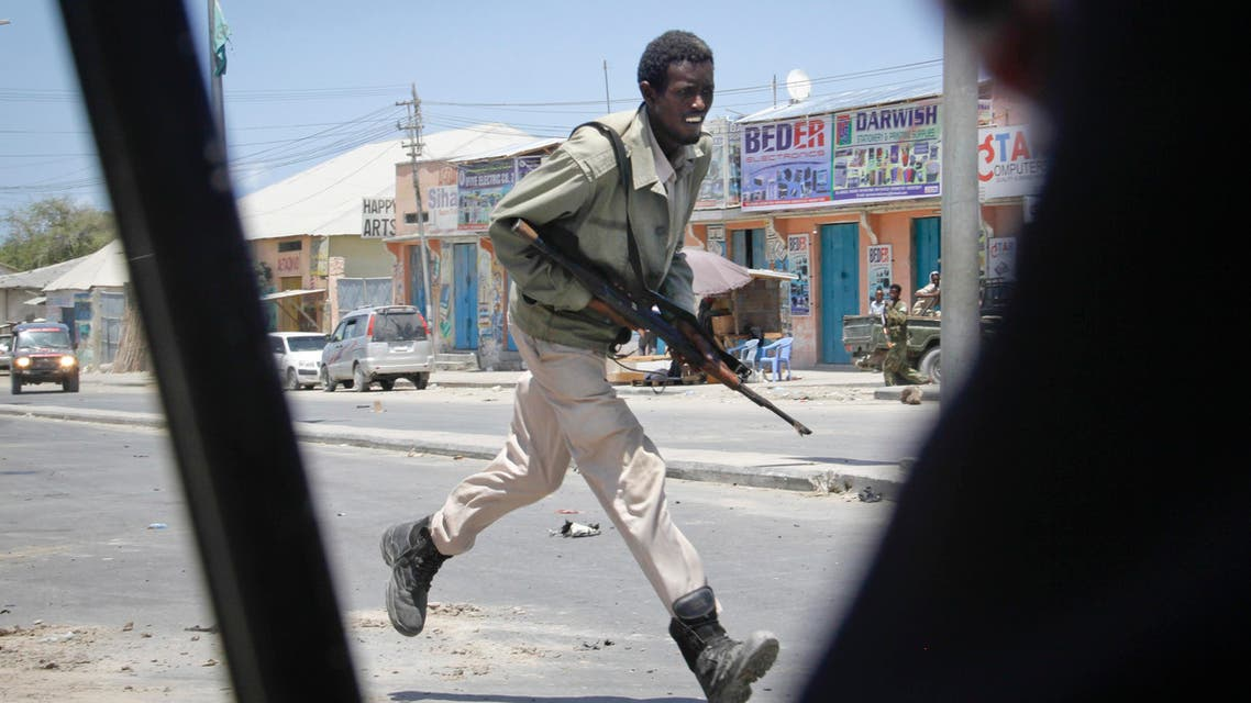 A Somali soldier runs during fighting following a car bomb that was detonated at the gates of a government office complex in the capital Mogadishu, Somalia Tuesday, April 14, 2015.  (AP)