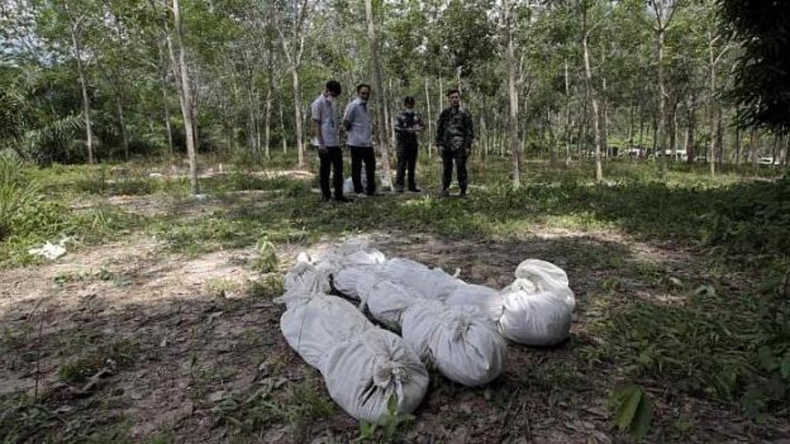 Thai policemen take notes behind human remains retrieved from a mass grave at a rubber plantation near a mountain in Thailand's southern Songkhla province on May 6, 2015. Malaysian police have discovered 30 mass graves in Perlis, believed to be linked to the mass graves found earlier this month in southern Thailand. -- PHOTO: REUTERS  - See more at: http://www.straitstimes.com/news/asia/south-east-asia/story/mass-graves-hundreds-dead-immigrants-found-perlis-report-20150524#sthash.JfBK1o15.dpuf