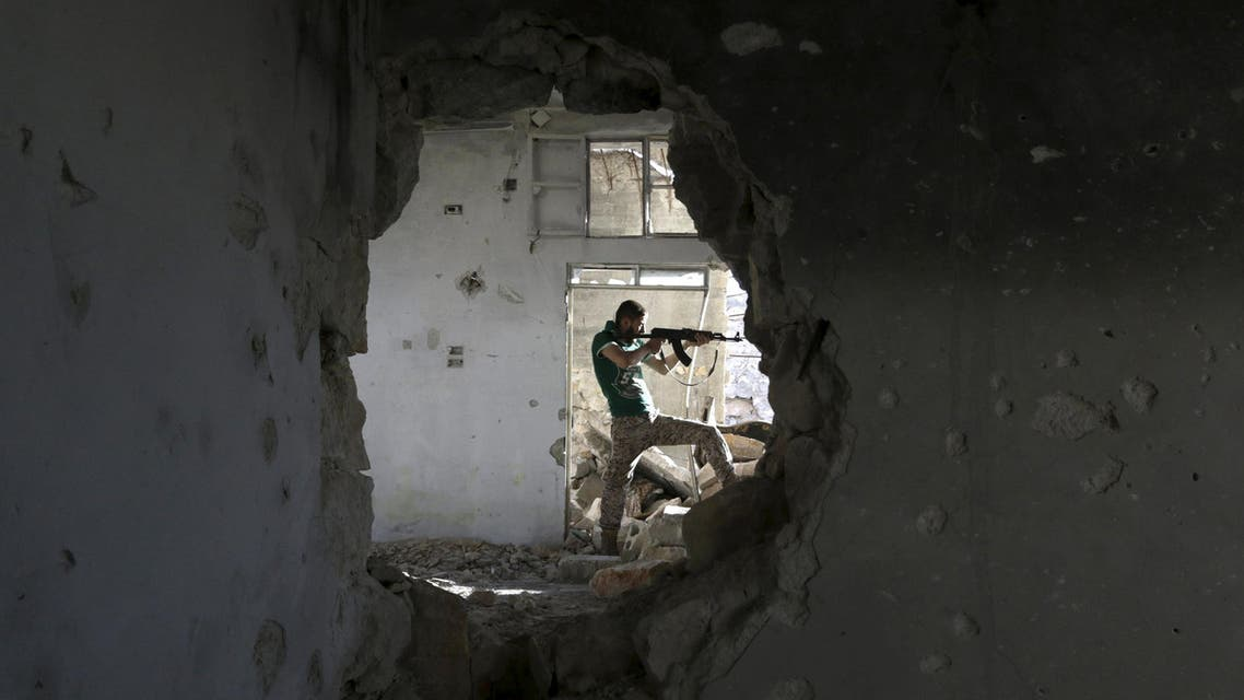 A Free Syrian Army fighter stands in a shooting position inside a damaged building during clashes with forces loyal to Syria's President Bashar al-Assad at the frontline in Handarat area, north of Aleppo. (Reuters)