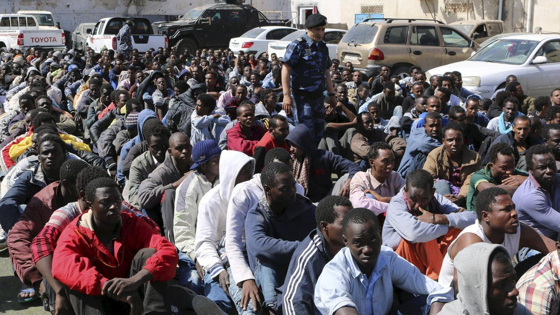 Migrants sit at a detention center after they were detained by the Libyan authorities in Tripoli, Libya May 17, 2015. Libyan authorities rounded up hundreds of migrants before they could head to European shores. REUTERS/Hani Amara