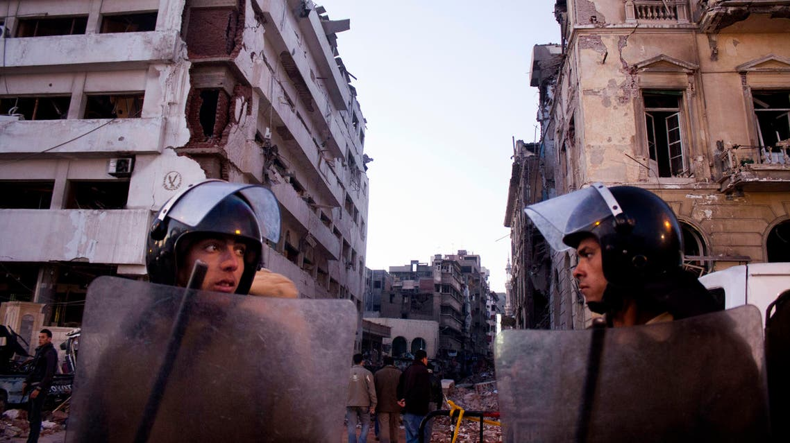In this file photo taken Tuesday, Dec. 24, 2013, Egyptian policemen stand guard at the scene of a powerful explosion believed to be a car bomb. (File: AP)