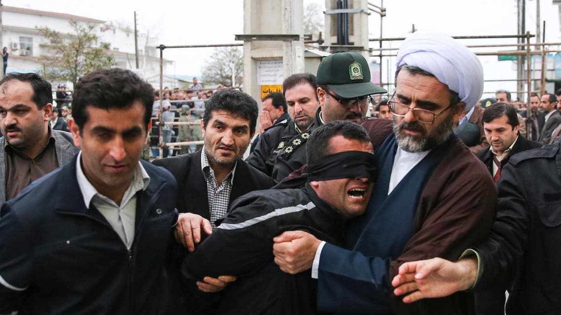 Iranian officials and security escorting away the blindfolded man Bilal from the scene of his execution in public in the northern city of Nour, Iran. (File: AP)