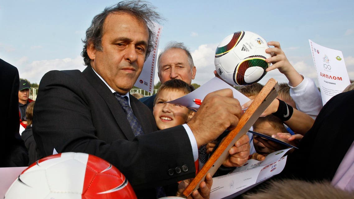 UEFA President Michel Platini, left, signs autographs after attending a ceremony to mark the start of construction of a national soccer team training center in Minsk, Belarus, Tuesday, Oct. 4, 2011. Platini is in Belarus to mark 100-years of Belarusian soccer. (AP Photo/Sergei Grits)