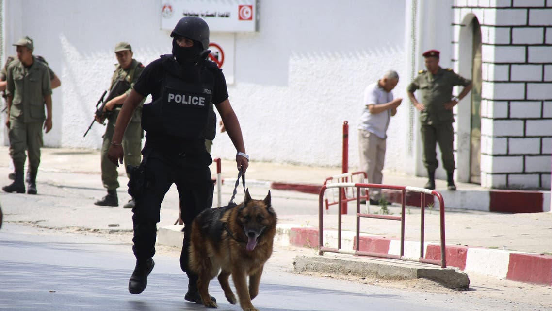 A Tunisian anti-terrorism brigade officer leads his dog after a shooting at the Bouchoucha military base in Tunis. (Reuters)