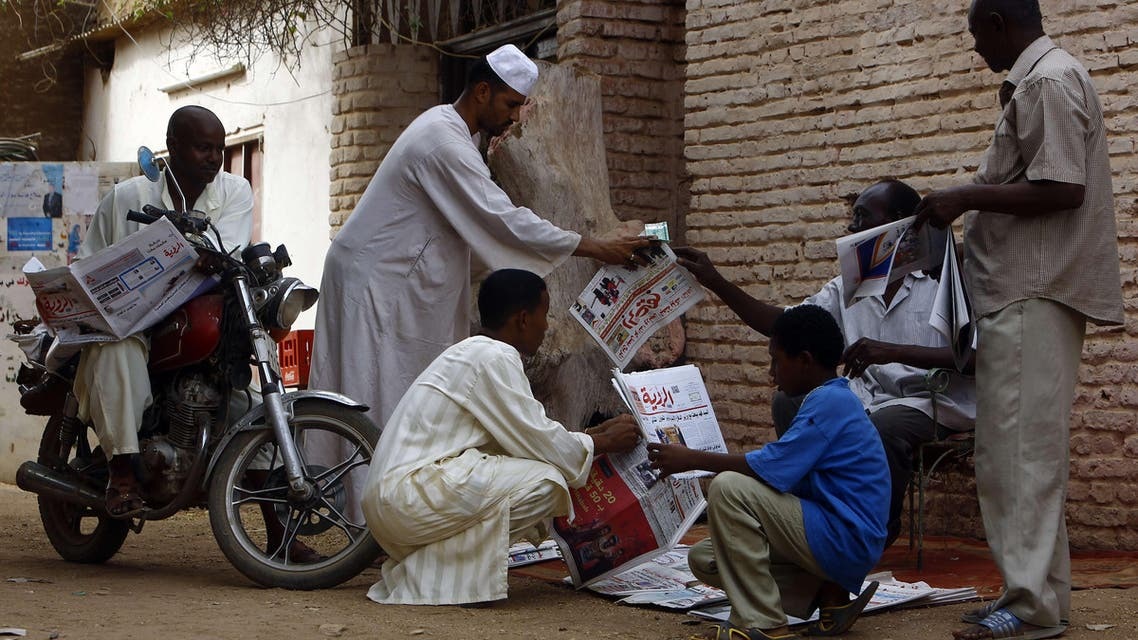 Sudanese men gather around a newspaper street vendor in a street in Al-Jarif city, outside the capital Khartoum, on May 25, 2015. Sudanese security forces seized the Monday print runs of nine newspapers and suspended the publishing licences of four of them in a major media crackdown, according to editors and an NGO. AFP PHOTO / ASHRAF SHAZLY