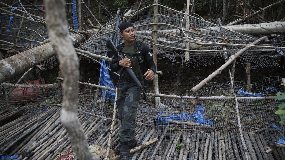 A policeman holds his weapon at abandoned human trafficking camp in the jungle close the Thailand border at Bukit Wang Burma in northern Malaysia May 26, 2015. (Reuters)