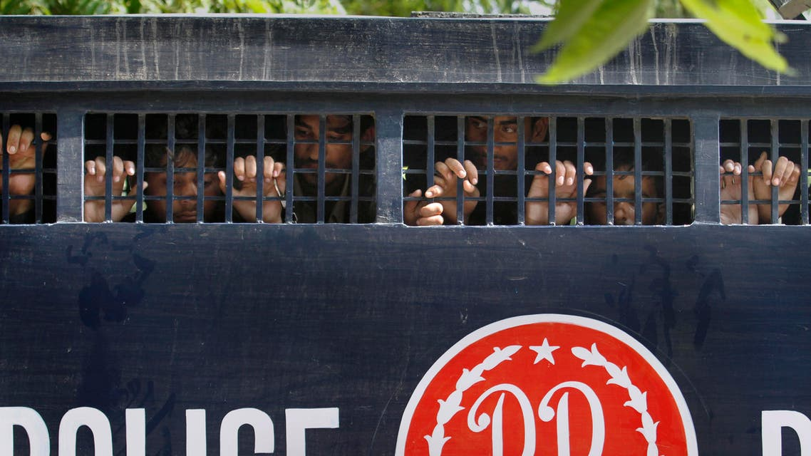 Detained anti-government activists peer out from a prison van after their court appearance in Islamabad, Pakistan, Saturday, Sept. 13, 2014. Pakistan's opposition said police have arrested scores of activists in an effort to stop them from participating in weekslong sit-ins in the capital, Islamabad. (AP Photo/Anjum Naveed)