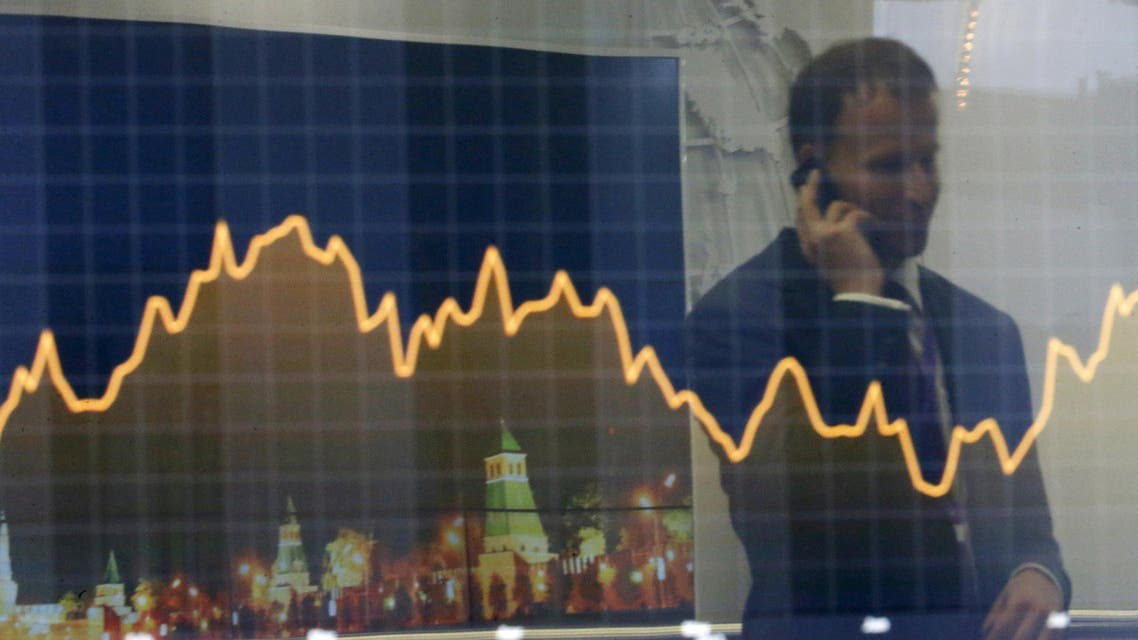 """A participant is reflected in a display showing business and financial information at the VTB Capital """"Russia Calling!"""" Investment Forum in Moscow in this October 2, 2014 file photo. Russian companies could return to international bond markets later in 2015 after being frozen out by Western sanctions over Ukraine as investor appetite for the high-yielding debt picks up. REUTERS/Maxim Shemetov/Files"""