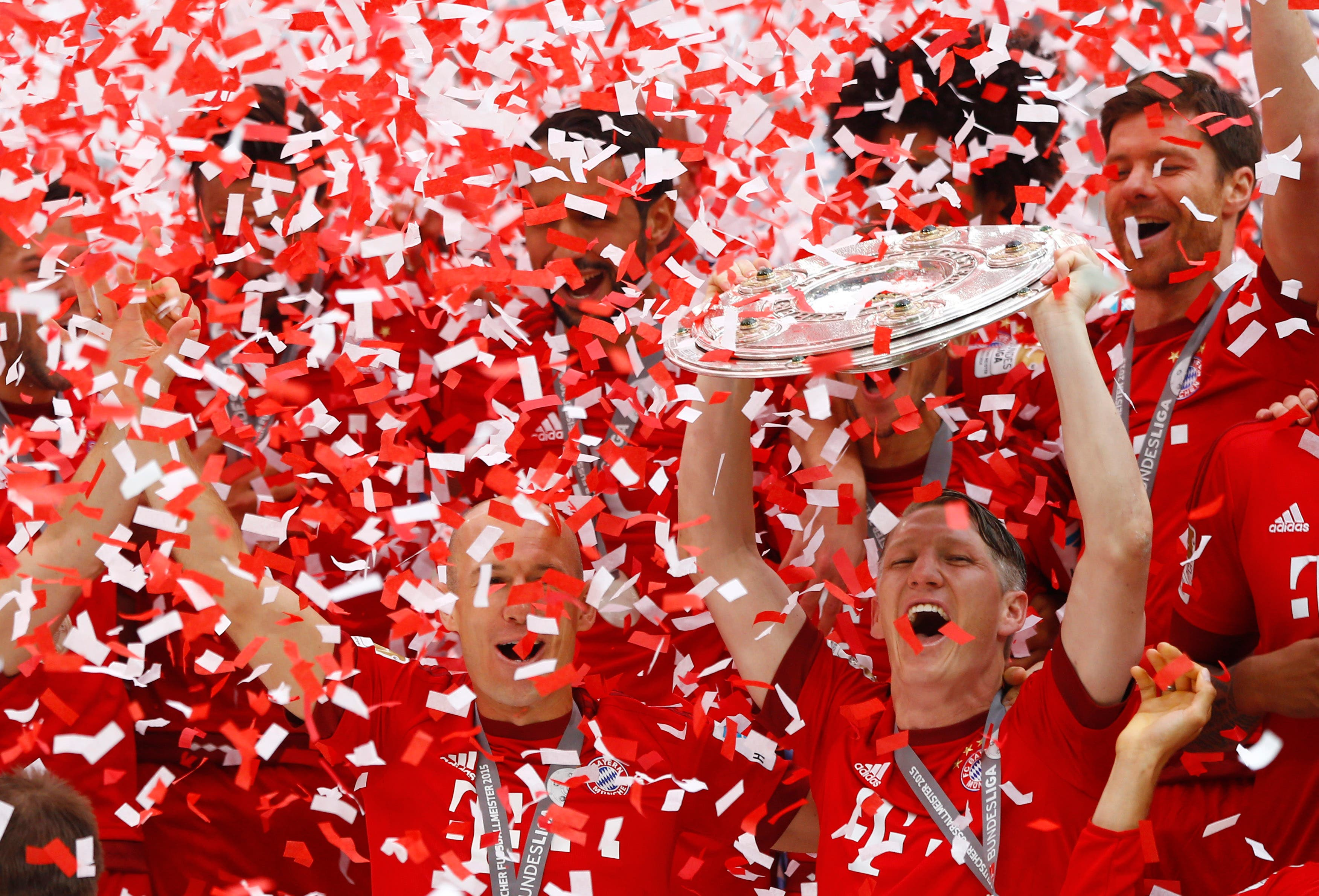Bayern's Bastian Schweinsteiger, bottom right, lifts the trophy as his teammates Bayern's Arjen Robben from the Netherlands, left, and Bayern's Xabi Alonso from Spain look on after the German first division Bundesliga soccer match between FC Bayern Munich and FSV Mainz 05 at the Allianz Arena in Munich, Germany, Saturday, May 23, 2015. (AP Photo/Matthias Schrader)