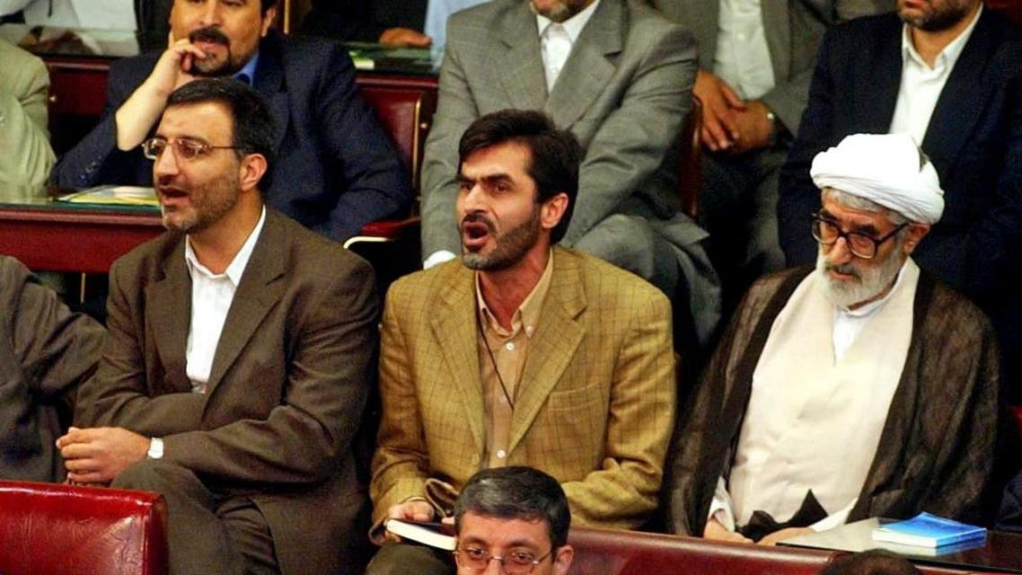 """FILE - In this file photo taken Thursday, May 27, 2004, Iranian hard-line lawmaker Mahdi Kouchakzadeh, center, chants anti-U.S slogans (Death to the U.S) in protest against the U.S-led coalition in Iraq, during an opening ceremony of parliament dominated by the conservatives who won a majority of seats in the disputed February elections, in Tehran, Iran. As Iran's nuclear negotiators returned home with the framework of a deal with world powers, joyous revelers joked that """"still, there is no whiskey"""" in the Islamic Republic, a jab at its theocratic government. But hard-liners here aren't laughing. Kouchakzadeh took the fight to parliament Sunday, April 5, 2015 holding up a placard reading: """"Any contract that brings foreign domination ... is forbidden."""" (AP Photo/Vahid Salemi, File)"""