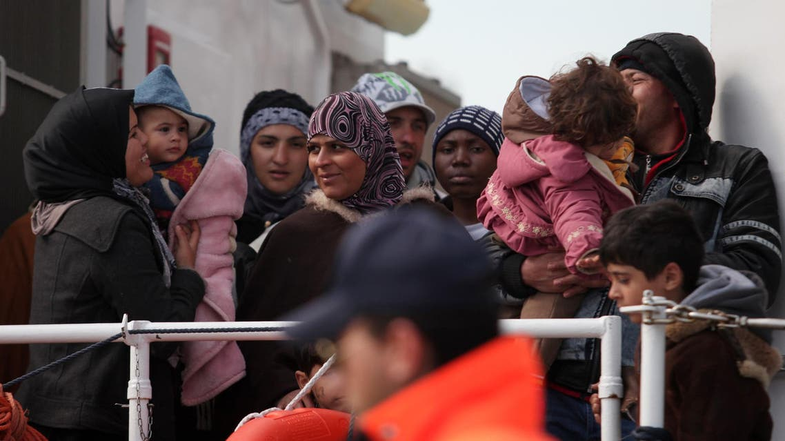 FILE - In this Wednesday, March 4, 2015, file photo rescued migrants wait to disembark from an Italian Coast Guard vessel in Porto Empedocle, Sicily, southern Italy. In a dramatic sea rescue north of Libya, a flotilla of rescue ships saved nearly 1,000 migrants and refugees, while 10 migrants perished in the southern Mediterranean. European Union countries are immersed in a full-fledged migration crisis. With the EU lacking funds and resources, some officials are even floating the idea of a multinational border guard to deal with arrivals of hundreds of thousands from war-torn countries like Syria, poor African nations and non EU neighbors like Kosovo. (AP Photo/Francesco Malavolta, File)