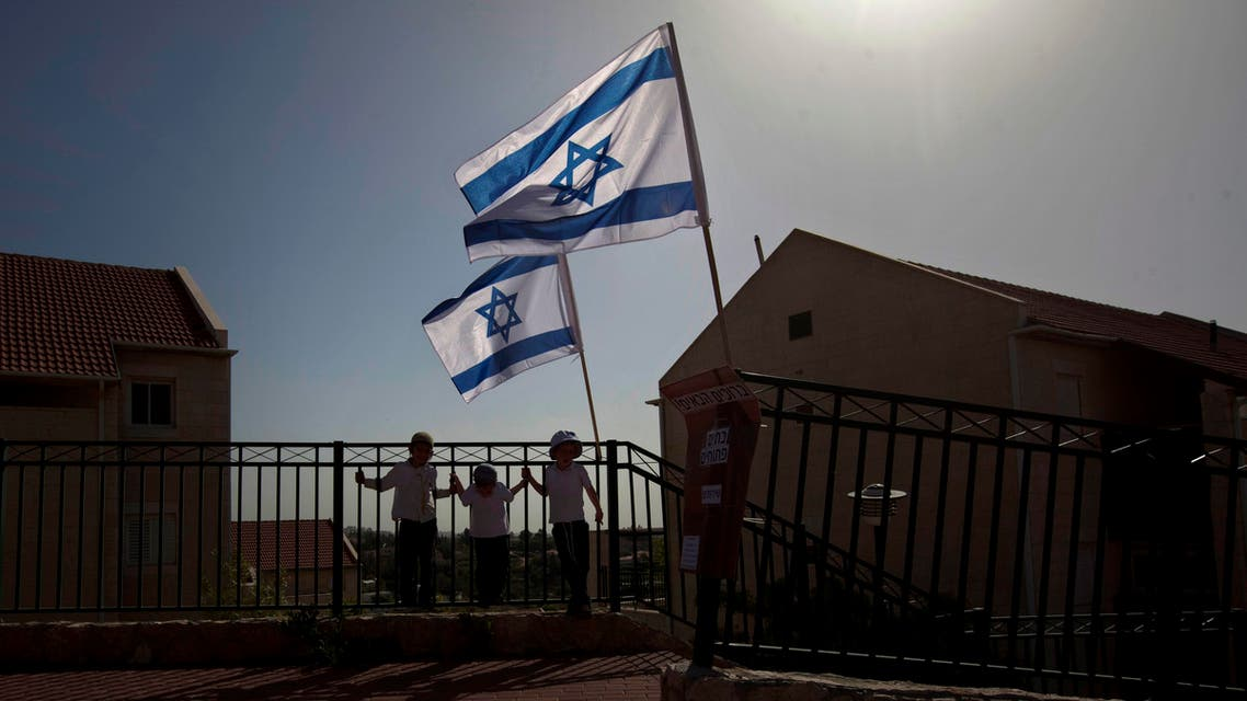 In this Sunday, April 22, 2012 file photo, Israeli flags fly over the Ulpana neighborhood in the West Bank settlement of Beit El near Ramallah.  AP