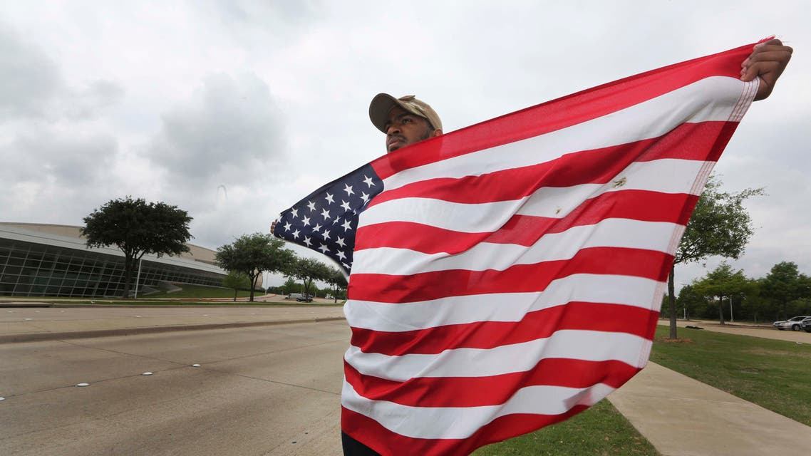 Joseph Offutt, 20, holds a U.S. flag across the street from the Curtis Culwell Center, where ISIS claimed responsibility for an attack by two gunmen. (File: AP)